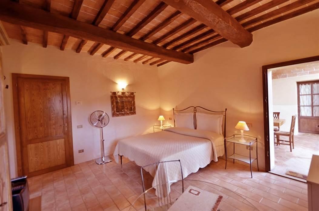 camera con letto in ferro battuto toscano